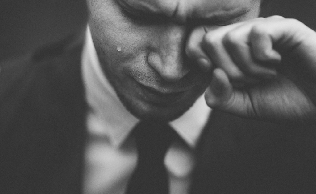 photograph of a man in a suit and tie, crying. Photo by Tom Pumford, from Unsplash.